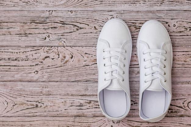 Mette in mostra le scarpe da ginnastica bianche su un pavimento di legno colorato