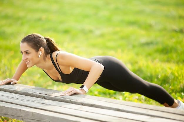 Donna sportiva facendo esercizi in panchina e ascoltando musica nell'ambiente urbano