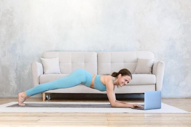 Donna di sport che fa sport online utilizzando laptop da casa a praticare yoga