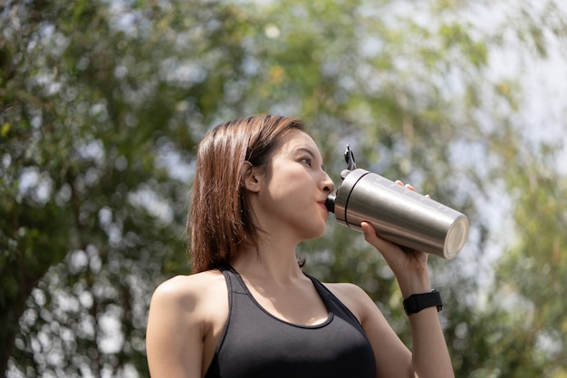 La donna sportiva beve il frullato proteico dallo shaker per bottiglie in acciaio inossidabile