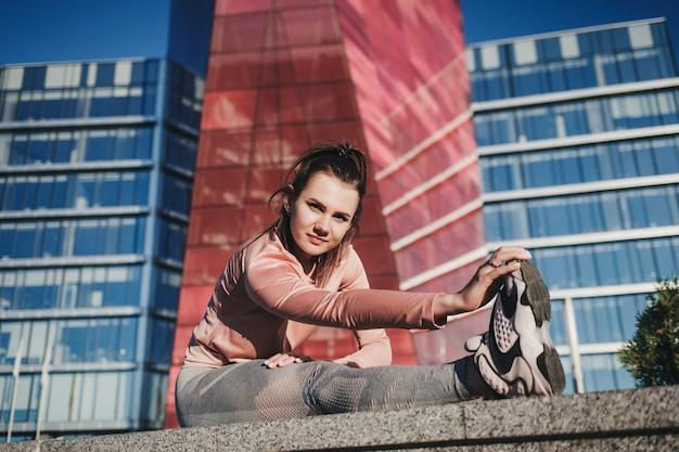Gli sport. donna in palestra facendo esercizi di stretching in città e sorridendo