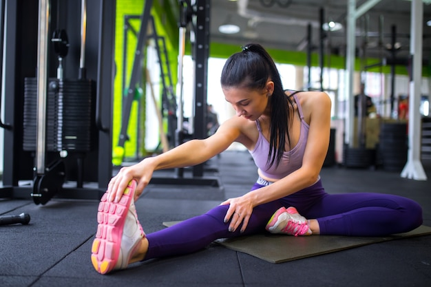 Gli sport. donna in palestra facendo esercizi di stretching e sorridente sul pavimento.