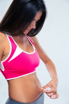 Donna di sport che tocca il suo grasso della pancia