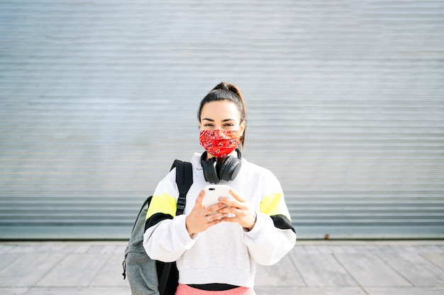 Donna sportiva con maschera che ascolta la musica con le cuffie e lo smartphone