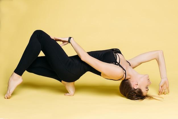 Mette in mostra la giovane donna che fa exersice dallo yoga.