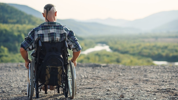 Sportivo dopo un infortunio in sedia a rotelle godersi l'aria fresca in montagna. riabilitazione di persone con disabilità.