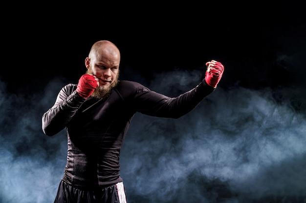 Combattimento del pugile dello sportivo sulla parete nera con fumo. concetto di sport boxe