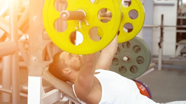 Sportivo facendo panca bilanciere premendo durante l'esercizio presso il fitness club. uomo muscoloso che si esercita in palestra, luce solare