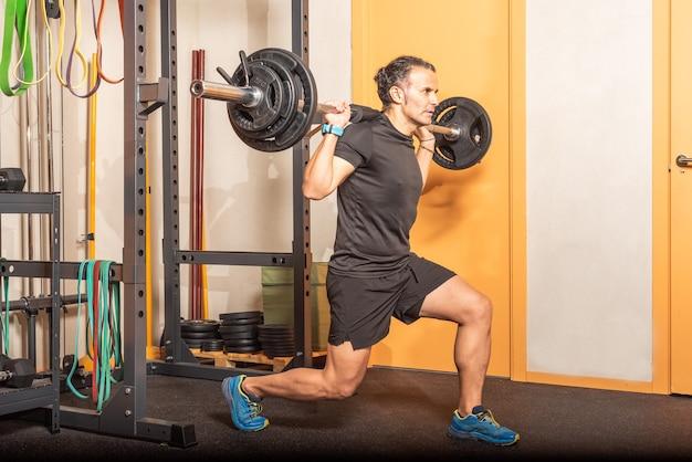 Sportivo facendo squat con bellbar in palestra. concetto di esercizio in palestra.