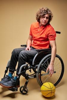 Lo sportivo ha dovuto rinunciare allo sport a causa della disabilità, si siede sulla sedia a rotelle, guarda la palla con un'espressione triste sul viso.