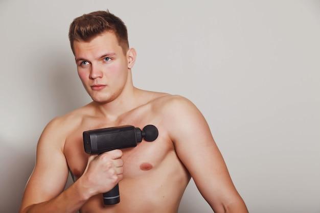 Lo sportivo tiene il massaggio d'urto della pistola sportiva nell'ufficio medico della palestra. esercizi di massaggio a casa dell'atleta. terapia a percussione per il massaggio rigenerante del corpo. concetto di riabilitazione da lesioni. copia spazio