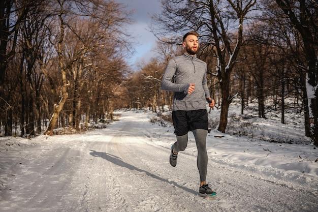 Sportivo a fare jogging nella foresta sul sentiero innevato in inverno.