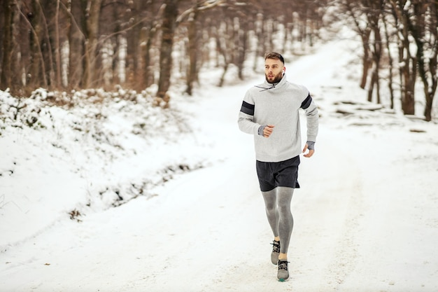 Sportivo a fare jogging in natura sulla neve in inverno. stile di vita sano, fitness invernale, freddo