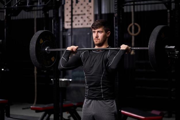 Sportsman sollevamento bilanciere in cross fit palestra, bodybuilding e concetto di sollevamento pesi. maschio in abbigliamento sportivo impegnato in allenamento crossft, allenamento da solo