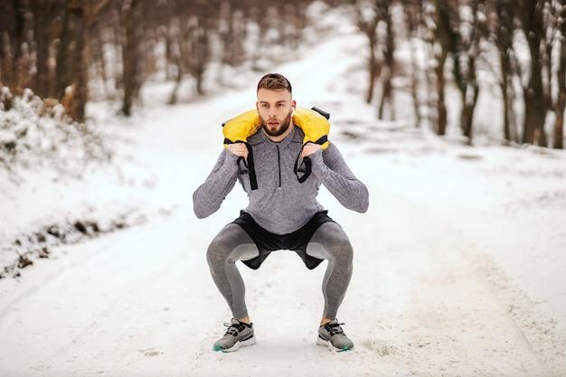 Sportivo sollevamento pesi in natura in caso di neve in natura.