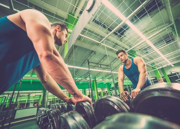 Lo sportivo si guarda allo specchio nel fitness club