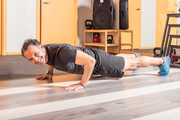 Sportivo che guarda l'obbiettivo con un sorriso facendo flessioni in palestra. concetto di esercizi in palestra.