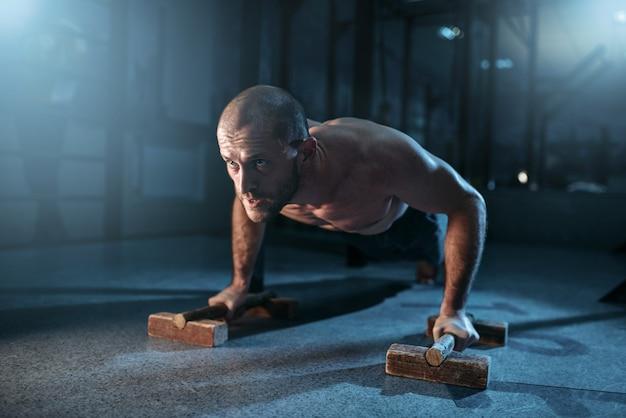 Lo sportivo fa esercizi di flessione sulle braccia durante l'allenamento