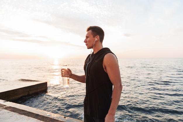 Sportivo all'aperto in spiaggia ascoltando musica con auricolari acqua potabile.