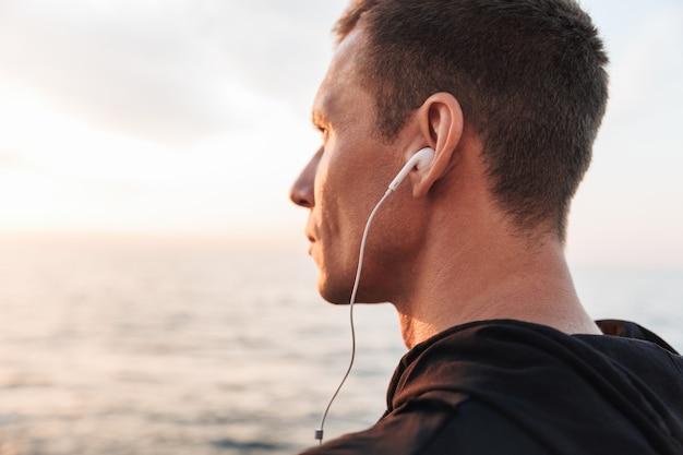 Sportivo all'aperto in spiaggia ascoltando musica con gli auricolari.