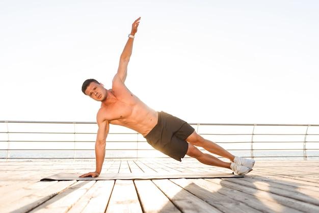 Lo sportivo all'aperto sulla spiaggia fa esercizi sul tappeto sportivo.