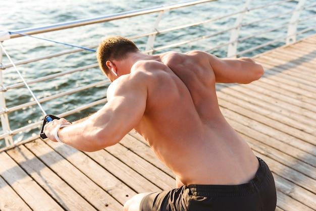 Lo sportivo all'aperto sulla spiaggia fa esercizi con attrezzature sportive.