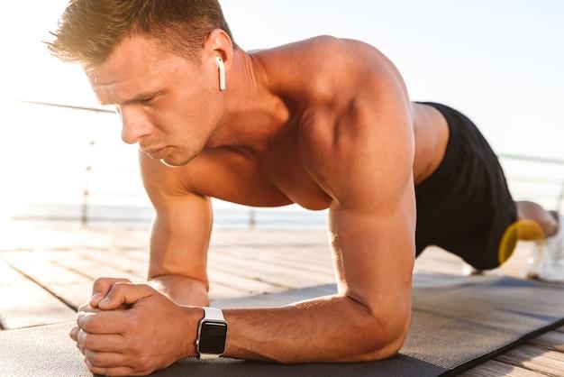 Lo sportivo all'aperto sulla spiaggia fa esercizi