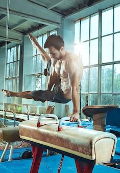 Lo sportivo che esegue un esercizio ginnico difficile in palestra. lo sport, l'esercizio, la ginnasta, la salute, l'allenamento, il concetto di atleta. modello in forma caucasica
