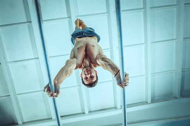 Lo sportivo che esegue un esercizio ginnico difficile in palestra il ginnasta dell'esercizio sportivo