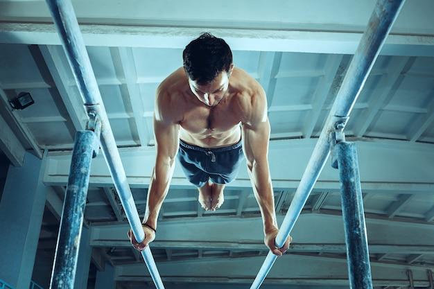 Lo sportivo che esegue un esercizio ginnico difficile in palestra l'esercizio sportivo