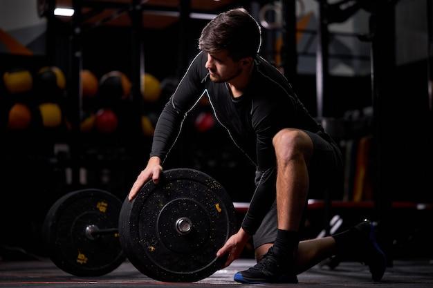 Powerlifter sportivo che si prepara per lo stacco del bilanciere durante la competizione, trascorre del tempo in palestra da solo, cambiando barra pesante, concetto di allenamento cross fit