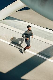 Sportivo che corre lungo la strada