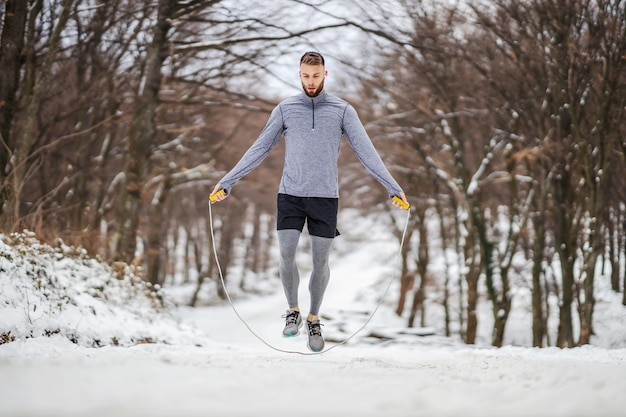 Sportivo in forma saltando la corda in natura sulla neve in inverno