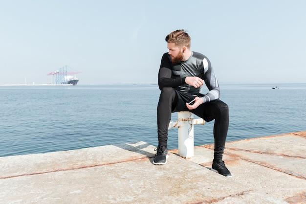 Sportivo seduto vicino al mare. guardando lontano