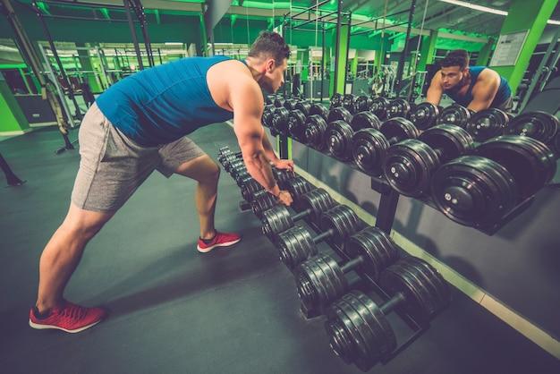 Lo sportivo prende un manubrio nel fitness club