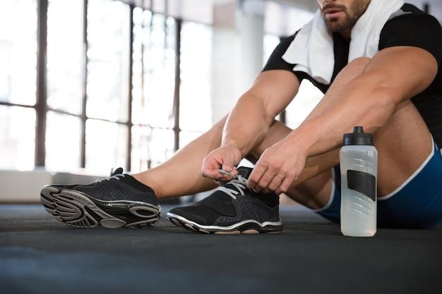 Lo sportivo si allaccia le scarpe da ginnastica nere Foto Premium