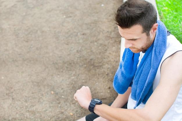 Sportivo che guarda l'orologio nel parco