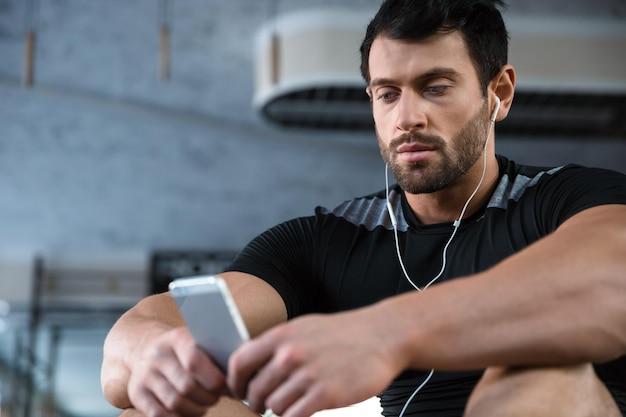 Sportivo che indossa una maglietta nera usando il cellulare e ascoltando musica