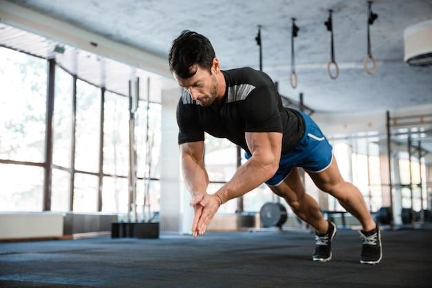Sportivo che indossa pantaloncini blu e maglietta nera che fa puch-up battendo le mani