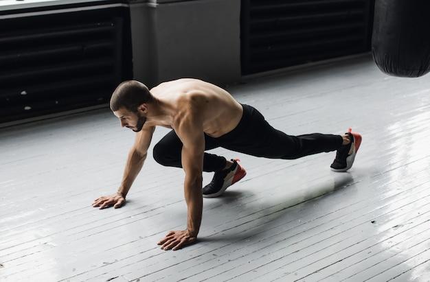Sportivo che indossa pantaloncini scuri facendo flessioni. foto di alta qualità