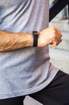 Lo sportivo con una bottiglia d'acqua sta riposando e controllando il suo orologio intelligente dopo aver corso