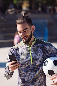 Sportivo con un pallone da calcio che consulta il suo telefono