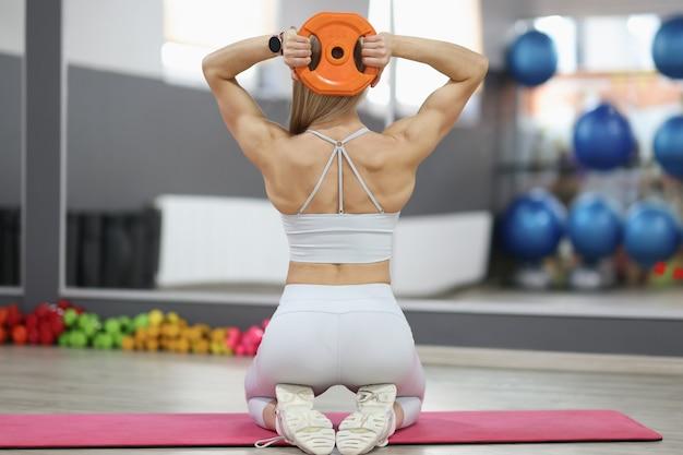 La sportiva fa esercizi sui muscoli della schiena con manubri tondi