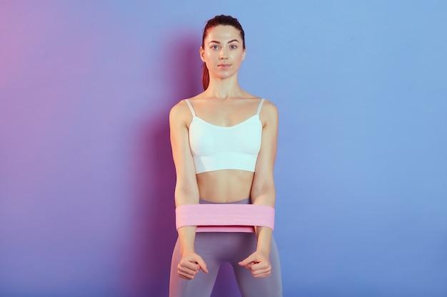 Sportiva che fa esercizio per i muscoli delle mani con fascia di resistenza