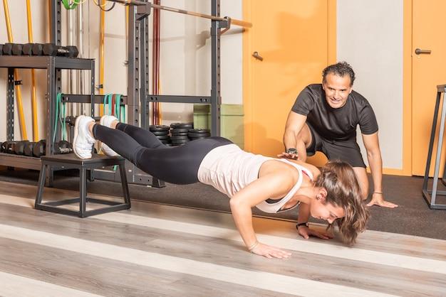 Sportiva facendo push up con i piedi sulla scatola con trainer in palestra. concetto di esercizi in palestra.