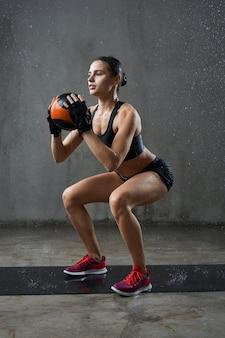 Sportiva che fa squat usando la palla