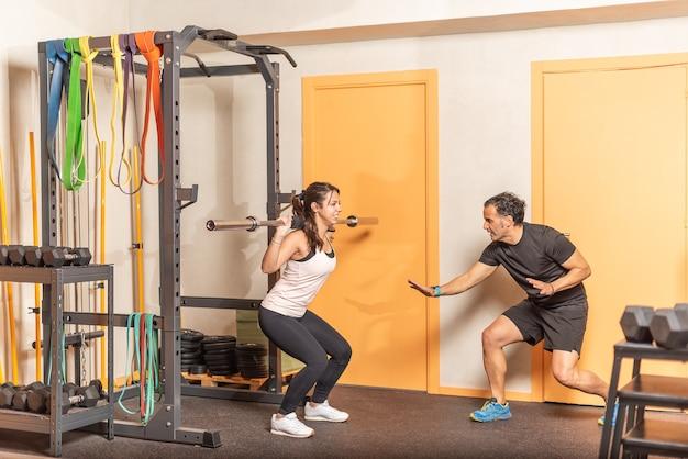 Sportiva facendo squat con bar con trainer in palestra. concetto di esercizio in palestra.