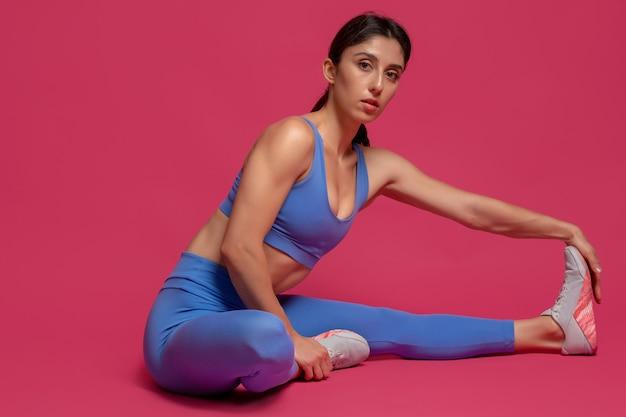 Sportiva che fa esercizi di stretching sul pavimento su superficie marrone rossiccio