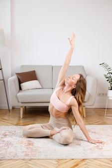 Sportiva che fa yoga in soggiorno
