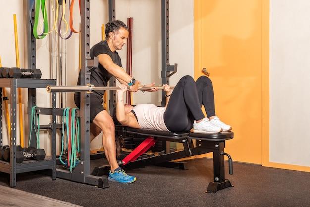 Sportiva che si esercita sulla panca da bar in una palestra con l'aiuto dell'allenatore. concetto di esercizi con attrezzature in palestra.